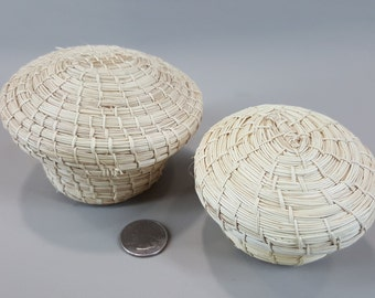 Pair of small woven grass baskets with lids