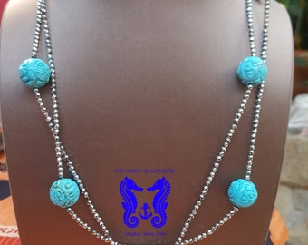 Long necklace of carved turquoise and hematite silver