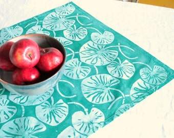 turquoise lilypad tea towel with a tab hand printed, hand dyed fabric