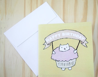 """CARD: """"Cupcake Cat"""" featuring a cat in a stupidly cute cupcake suit, holding a Happy Birthday banner"""