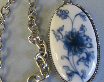 Handmade blue flower patterned ceramic pendant necklace with silver tone chain and lobster clasp closure