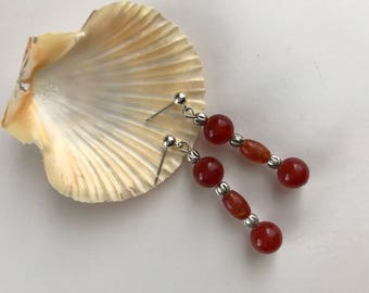 Carnelian drop earrings, with three beads dangling from silver-plated ear posts.