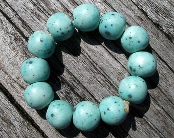 A strand of 12 multi color ceramic round beads in robin's egg blue