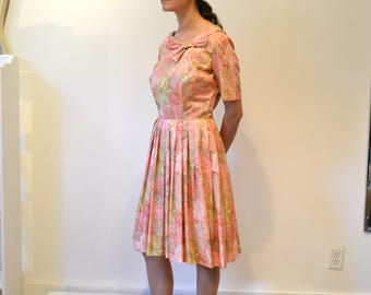 1950's Pink Floral Printed Day Dress. Pleated Skirt, Collar with Bow, Short Sleeves. Size Small-Medium. Side Zipper.