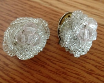 Pair of large, vintage clip on earrings.  Made with frosted seed beads, surrounding a cluster of clear beads. vintage clip earrings, beaded