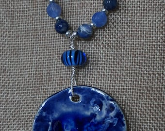 Stunning ceramic pendant glazed in blue with melted blue glass on top.