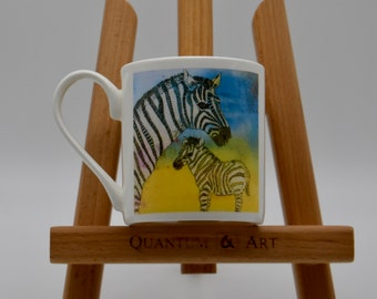A vibrant, colourful bone china mug featuring a zebra and foal, original artwork