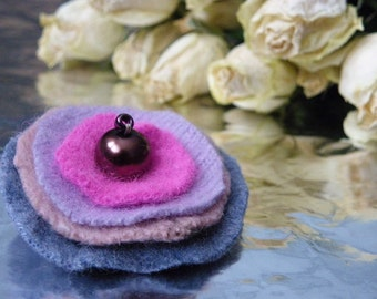 Round colorful handmade brooch from recycled wool sweaters with glass bead