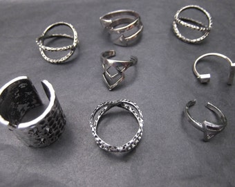 Silver coloured metal dress rings, beautiful, adjustable, 8, one for every day of week.