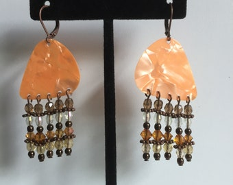 apricot marbled guitar pick with fives strands of glass, crystal and metal beads.