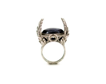 The Witch's Ring in Old Steel - An enchanting ring with sprays of feathers engulfing a Goldstone gemstone.