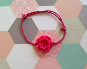 Child's charm bracelet with pink carved mounted on a raspberry pink adjustable cord