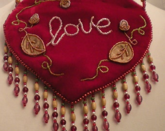 Heart shaped purse that says LOVE on the front