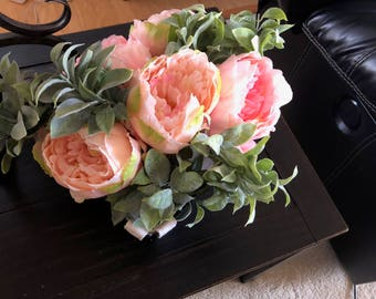 Pink and coral peony floral arrangement with soft greenery in a wire basket