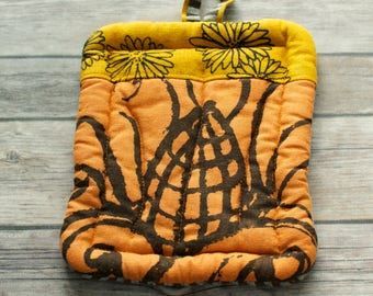 small bright orange and gold yellow hot pad hand dyed and printed with with corn and flowers