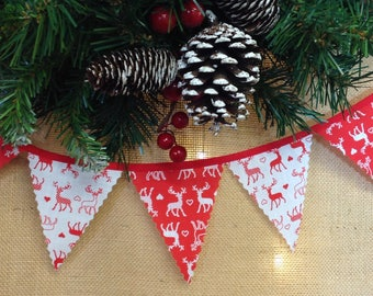 Nordic mini bunting with red and white stags attached to red tape, perfect for a traditional Christmas