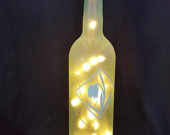 Frosted bottle light with blue flower decoration.