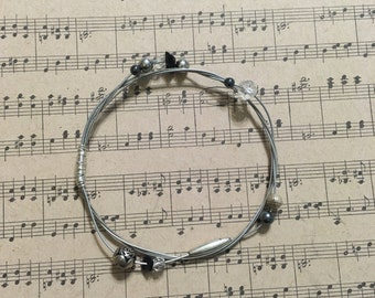 Reused silver guitar string bangle bracelet adorned with hematite, quartz, czech crystals, and silver beads
