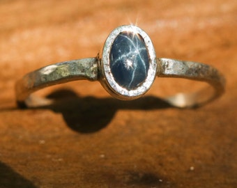 Oval blue star sapphire ring in silver bezel setting with sterling silver texture flat band