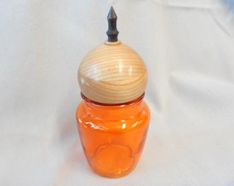 By graduation gift, An orange glass utility jar with a wood lid and black finial at the top