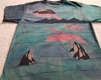 Orca whales checking out the sun and clouds, mountains, reflections on the water, man's large discharged & dyed t-shirt, blues and pink