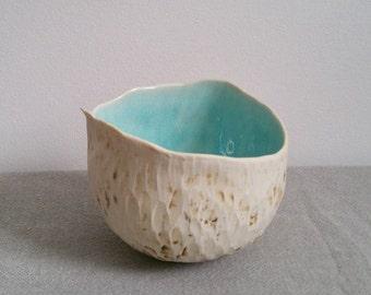Round organic pinch pot bowl with aqua in glazed interior.