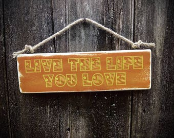Handmade wooden sign with the words 'live the life you love'.