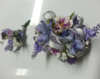 Silver rhinestone wrist corsage and matching boutonnière set made with realistic-looking assorted purple flowers. White and silver ribbon.