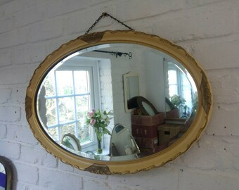 Large vintage gesso style guilt mirror with handpainted plaster frame and bevelled glass edges.