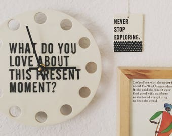 """porcelain clock 8.5"""" screenprinted text what do you love about this present moment."""