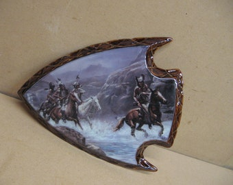 Indians in the river with funky head dresses, on a arrowhead frame.