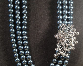 """On sale, Was 35 now 25... 16"""" 3 strand Blue/grey glass pearl necklace with vintage rhinestone focal piece with matching earrings on posts."""