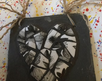 Black and white broken china mosaic heart on slate