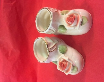 Pair of white ceramic booties with roses on top