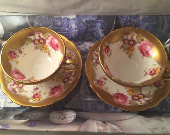 Two matching vintage cups and saucers.