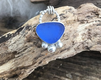 Scottish sea glass in cobalt  blue bezel set in fine sterling silver on 20 inch chain .