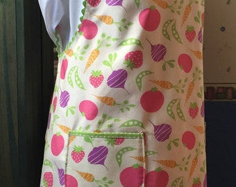 Vintage style full coverage apron done in quality cotton with colorful fruits and vegetables in green, pink, purple and orange on off white.