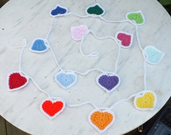 """Crocheted """"hearts"""" bunting, in rainbow colours each with a white border and joining chain."""