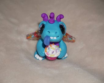 Polymer clay blue candy sprinkle wing dragon holding a yummy sprinkle cupcake