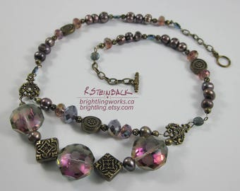 Mauve Spectrum Necklace; Bronze Purples Greens in Various Shapes & Hues of Textured Metal, Cut Glass, Freshwater Pearls with a Toggle Clasp