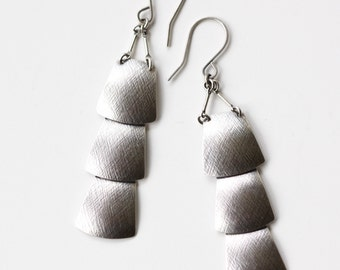"Sterling silver veil earrings of three dramatically connected trapezoid shapes each of which is textured and domed - ""Drape Earrings"""