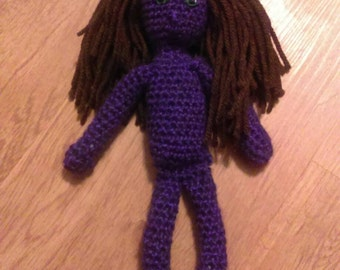 Crocheted purple doll with brown hair and green eyes