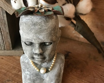 Vintage porcelain doll bust with a look of aged concrete