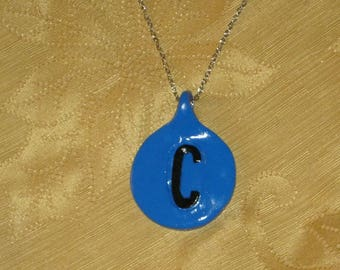 Circle that comes in seven colors, with one personalized black capital initial raised design pendant necklace