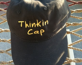 "Thinkin Cap - Black w/Gold Lettering - Reverses to say ""Not Thinkin"" on the back"