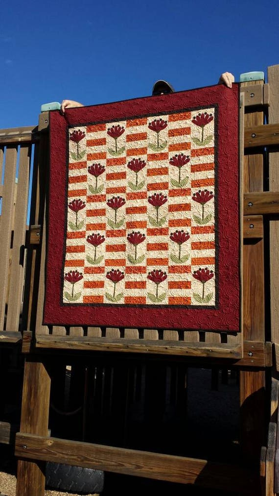 Autumn Lap Quilt Kit. Bold Applique Red Flowers On Stems Surrounded By Fall Orange And Cream Prints Framed In Deep Red Dots, Black Binding