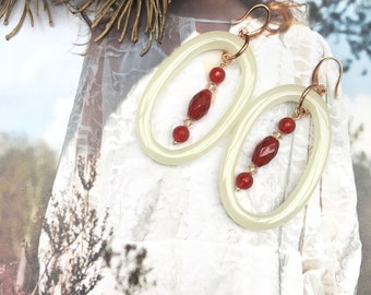 Perky. Beautiful handmade earrings with polyresine pendant in the color creme, with Edelsteentjes carnelian and Swarovski.