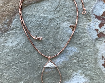Boho style beaded chain with a copper oval pendant with silver accents