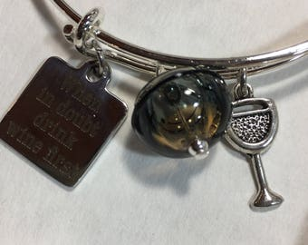 Bracelet, adjustable silver plated bangle When in Doubt, Drink Wine First word print with hollow lampwork bead, and wineglass charm