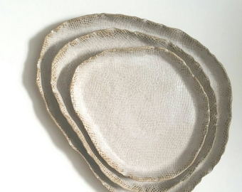 Set of 3 textured stoneware nesting plates.  Dinnerware or food photography props.  Earthy, rustic organic plates in beige and white.